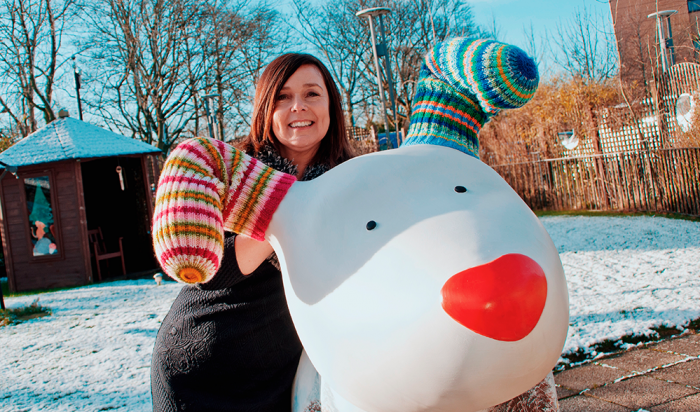 Jane Hogan, poses with giant Snowdog sculpture in a snowy garden
